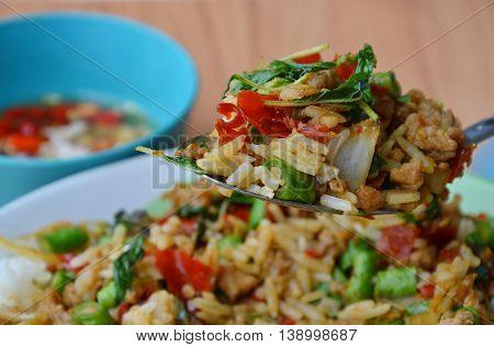 stir-fried spicy chop pork with basil leaf and rice on spoon