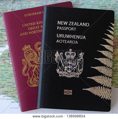 Two passports - United Kingdom UK and New Zealand NZ - on a map of England representing dual nationality or citizenship.