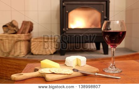 Cosy evening at home with red wine brie or camembert cheese and crackers in front of a fire in a woodburner or wood burning stove with logs next to it.