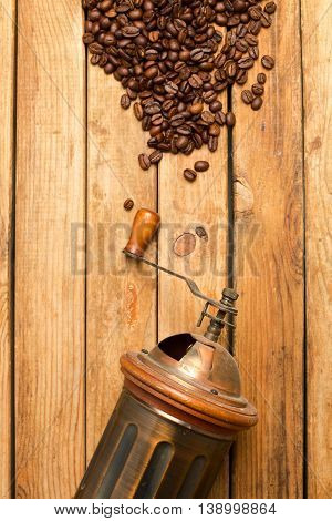 Vintage grinder and coffee over wooden table background