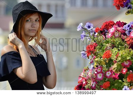 summer red-haired girl in a black hat and a black tank top on a background of flowers hand holds her hat
