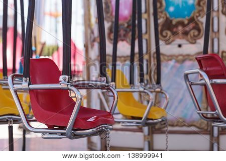Colorful swing carousel carnival chair ride on a fairground in summer.