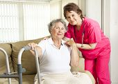 Friendly nurse cares for an elderly woman in a nursing home.
