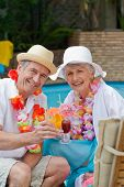 foto of summer fun  - Happy senior couple drinking cocktail and toasting each other - JPG