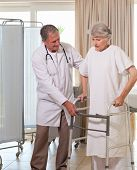 stock photo of zimmer frame  - Senior doctor helping his patient to walk - JPG