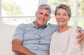 Smiling senior woman, and man sitting together on a sofa. Portrait of a candid older couple enjoying poster