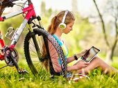 Bikes cycling girl. Girl rides bicycle. Girl wearing headset watch in pc tablet and listing music ne poster