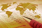 stock photo of international trade  - World outline map overlaid on financial newspaper - JPG