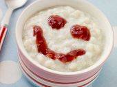 Bowl of Creamed Rice Pudding with a Strawberry Jam Face