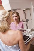 picture of mammogram  - Nurse Assisting Patient Undergoing Mammogram - JPG