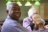 stock photo of senior adult  - Senior man playing bridge - JPG