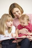 foto of girl reading book  - Mother And Daughters Reading Book - JPG