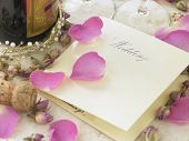 foto of wedding invitation  - Wedding Invitation Next To Champagne Bottle Surrounded By Flower Petals - JPG