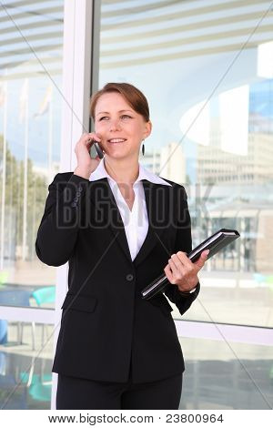 A pretty business woman at the office building on her cell phone