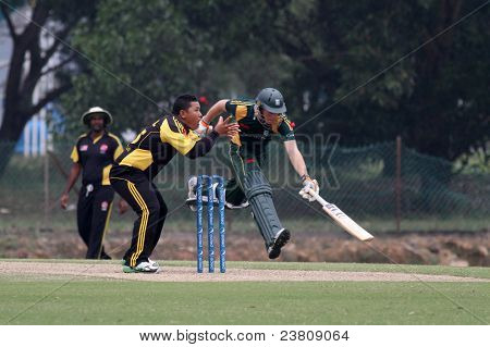 PUCHONG, MALAYSIA - SEPT 24: Guernsey's Ben Ferbrache runs in before the ball got to Malaysia's MN Azril, at the Pepsi ICC WCL Div 6 finals in Kinrara Oval on Sept 24, 2011 in Puchong, Malaysia.
