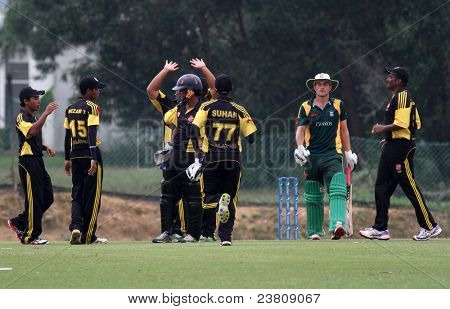 PUCHONG, MALAYSIA - SEPT 24: Malaysia's fielders celebrate Guernsey's Ross Kneller dismissal, at the Pepsi ICC World Cricket League Div 6 finals in Kinrara Oval on Sept 24, 2011 in Puchong, Malaysia.