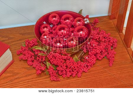 Bookcase Decorate With Red Christmas Balls In Bowl And Berries