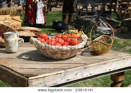 Produce and breads on rough hewn outdoor wooden table