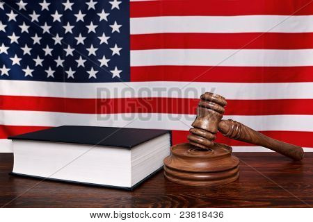 Still life photo of a gavel, block and law book on a judges bench with the American flag behind.