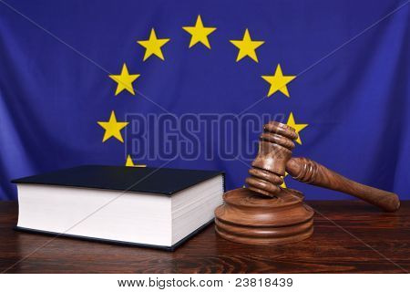 Still life photo of a gavel, block and law book on a judges bench with the European Union flag behind.