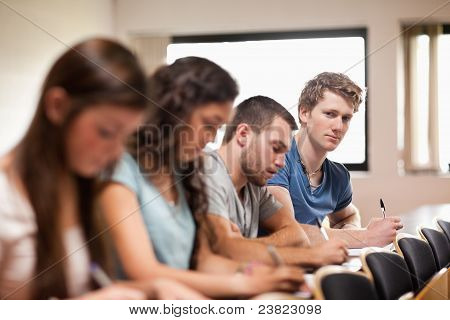 Studenten hören Dozent mit der Kamera im Mittelpunkt der Foreg