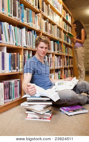 Portrait Of A Student Doing Research While His Classmate Is Read
