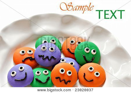 Plate of colorful little homemade cookie faces on white background with copy space.  Macro with shallow dof.