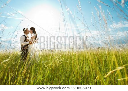 Kissing Bride And Groom In Sunny Grass