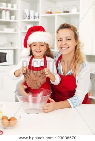 Happy woman and little girl at christmas time in the kitchen preparing cookies