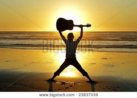 Gitarrist mit Sonnenuntergang am Strand