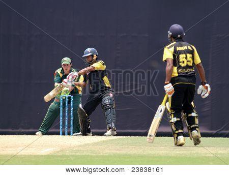 PUCHONG, MALAYSIA - SEPT 24: Malaysia's Aminuddin Ramly (55) eyes Mohd Safiq bat at the Pepsi ICC World Cricket League Div 6 finals vs Guernsey on Sept 24, 2011 at the Kinrara Oval, Puchong, Malaysia.