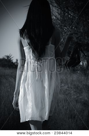 The Strange Mysterious Girl In White Dress With Shoes In Hand Is On The Field. Rear View, Black And