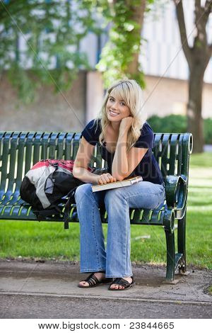 Portrait of young smiling female student sitting on bench at college campus