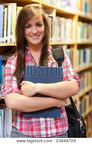 Portrait of a smiling female student posing in a library