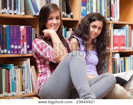 Female students holding a book in a library