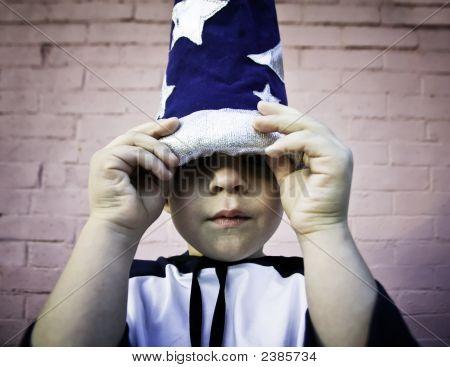 Menino olhando para fora de um chapéu de assistente