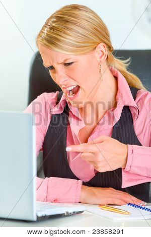 Angry Business Woman Sitting At Office Desk And Shouting On Laptop