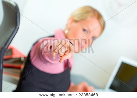 Modern Business Woman Sitting At Office Desk And Pointing On You