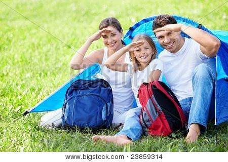 Smiling family with a backpack tent