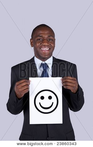 african businessman holding a happy face symbol printed on a paper