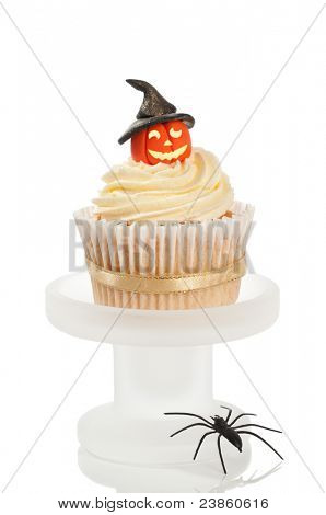 Halloween cupcake with pumpkin wearing a witches hat on a white background