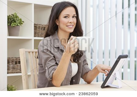 Beautiful, smiling, young brunette woman at home at a table using her tablet computer drinking a mug of tea or coffee