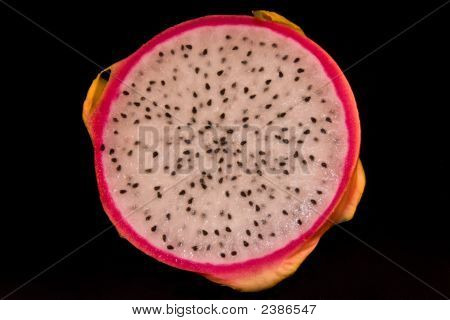 Dragon fruit sliced in half on a black