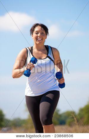 Talla grande mujer ejercicio al aire libre sonrisa bajo el soleado cielo azul
