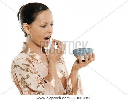 Portrait of beautiful Asian woman taking pill in studio isolated on white background