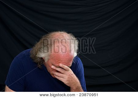 Man Looking Down And Covering Face With Hand