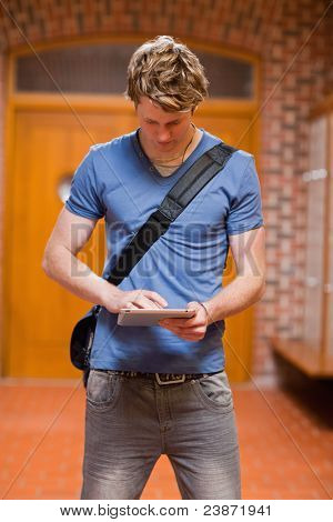 Portrait of a handsome student using a tablet computer in a corridor