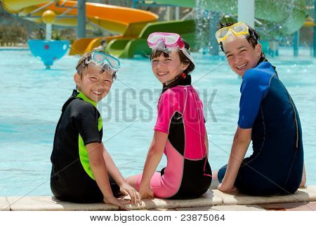Three kids sitting poolside