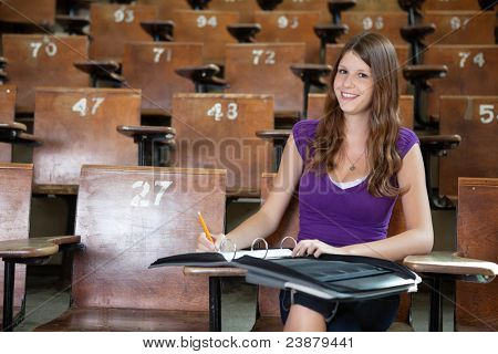 Portrait of young student completing assignment at university