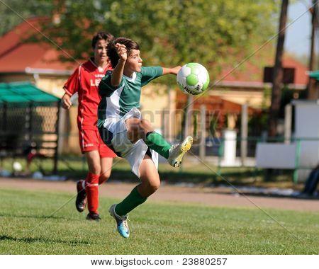 KAPOSVAR, HUNGARY - SEPTEMBER 11: Soma Ozorai (green) in action at the Hungarian National Championship under 15 game between Kaposvar (green)  and Lenti (red) September 11, 2011 in Kaposvar, Hungary.